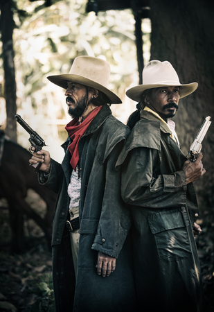 Close up Two cowboys standing and holding short gun in his farm Banco de Imagens