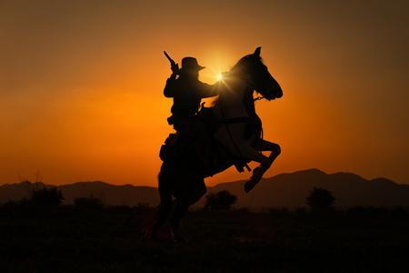 Vaquero de silueta sosteniendo una pistola corta y montando un caballo al amanecer.