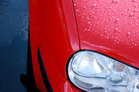 A red, new car with rain on the bonnet Stock Photo - 2678969