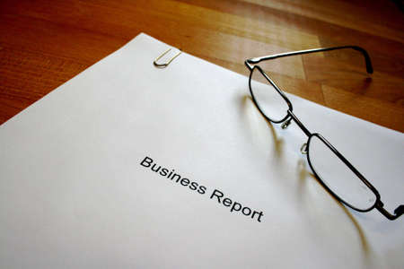 A business report and a pair of glasses Stock Photo