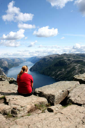 A woman sitting atop the Pulpit Rock, Norway Stock Photo