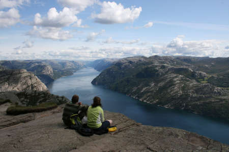 A couple resting atop the Pulpit Rock, Norway
