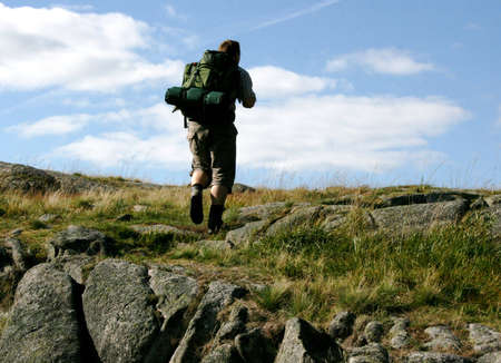 A man and his backpack walking in nature a sunny day