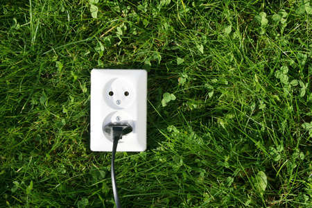 An electrical cord connected to an electrical socket that generates power from green grass or other relevant natural sources of energy Stock Photo