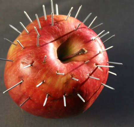 An apple full of nails Stock Photo