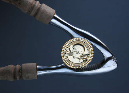 financial squeeze, money in a wrench, pirate coin in a nut cracker Stock Photo
