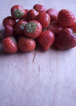 tast:  A fresh and juicy strawberry on a wooden table Stock Photo