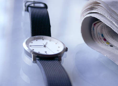 A wristwatch and a news paper on a table