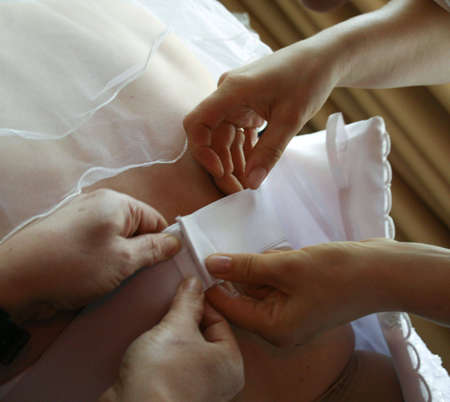 Several clever hands helping to fit the brides wedding dress Stock Photo