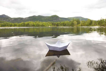 Paper boat floating on water Stock Photo