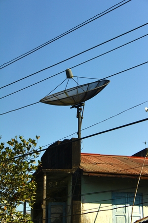 antena parabolica: The satellite dish and electric line on the street