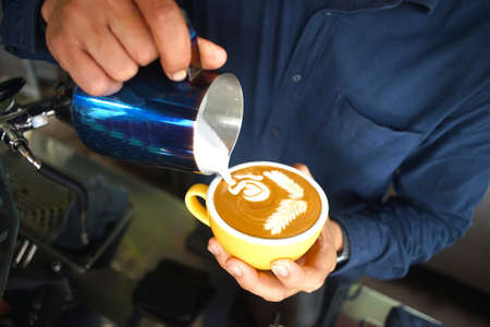 A man making latte art at cafe 스톡 콘텐츠
