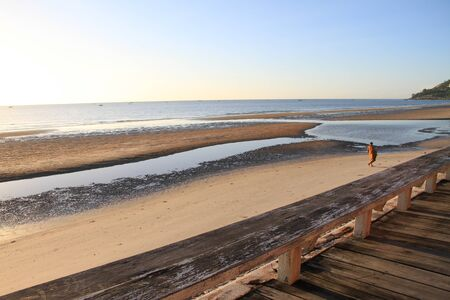 Monk walking on the beach, Sunrise photo