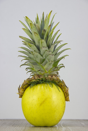 Pineapple hat on apple. Its the basis for drawing a funny human face.