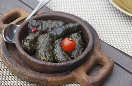 Traditional georgian dolma in grape leaves on rustic wooden table.
