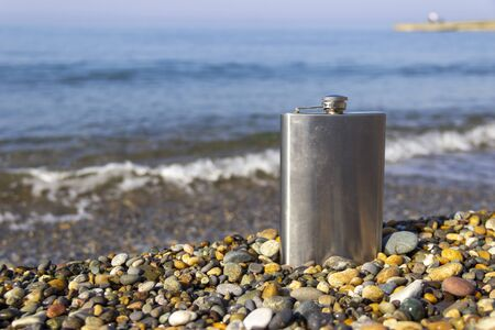 vintage metal hip flask on pebbles on a beach. celebration of men's holiday at sea. conception International Men's Day and Fatherland defender day February 23. copy space
