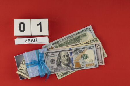 perpetual calendar with wooden cubes. the concept of celebrating the birthday of the dollar on April 01. dollar tied with a festive bow. American currency, paper currency notes. red holiday background