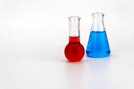 Laboratory glassware with liquid on white background. glass chemical flask with reagent. glass technical vessel used in chemical laboratories. Erlenmeyer flask is used in a trimetric analysis.