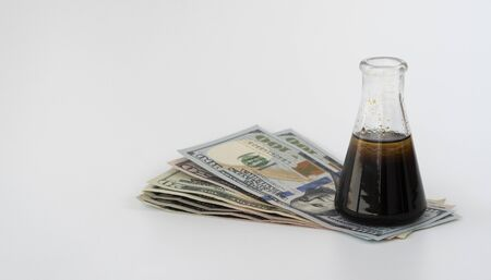 oil prices down. flask of oil and money isolated on a white background. the concept of the world oil market, falling prices. futures contract for the purchase or sale of petroleum products. Фото со стока