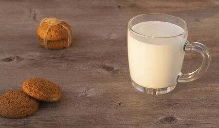 mug with milk and oatmeal cookies on a wooden background. great breakfast in the fresh air.