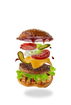 Delicious burger with flying ingredients isolated on white background. Food levitation concept. classic burger, assembled sandwich. preparing a quick meal, fast food products. copy space Standard-Bild