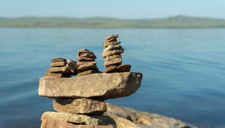 boat made of stones on the background of water. scenery on the shore of a beautiful lake.