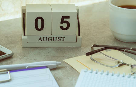 August 05, date on the calendar. Handmade wood cube with date month and day. planning for the day. Foto de archivo