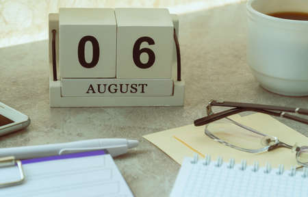 August 06, date on the calendar. Handmade wood cube with date month and day. planning for the day. artistic coloring. selective focus Foto de archivo