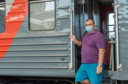 man in a medical mask near the train car. concept of travel during the pandemic. mode of permanent wearing of a protective medical mask. antiviral medical mask for protection against flu diseases.