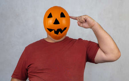 man in a Halloween mask on a white background. person with orange pumpkin evil mask. Jack lantern mask from a basketball. holiday concept