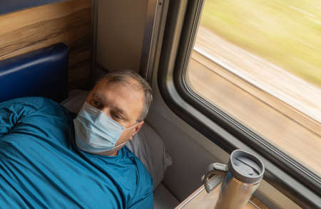 man in a medical mask near the train car. concept of travel during the pandemic. passenger is lying in his seat in the compartment of the car