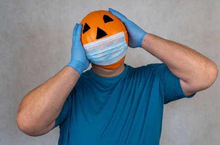 Halloween pumpkin in a medical mask. person with orange evil mask. Jack lantern mask from a basketball. Zdjęcie Seryjne