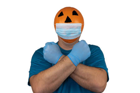 Halloween pumpkin in a medical respiratory bandage. Surgical protective mask. person with orange evil mask. Jack lantern mask from a basketball. celebrating Halloween during the quarantine period