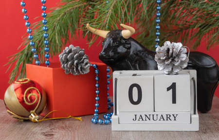 calendar with the date January 01 and a bull figurine. Handmade wood cube with date month and day. Festive Christmas decorations on a red background. bull as a symbol of the new year 2021.