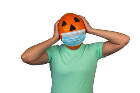 Halloween pumpkin in a medical mask. woman with orange evil mask. 写真素材