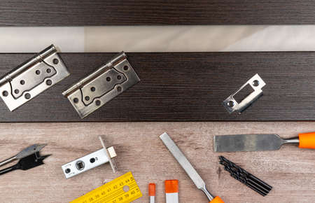 insert the lock into the interior door. joinery. tools and materials, top view, copy space
