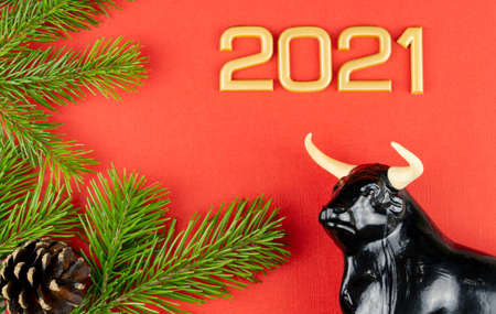 statuette of a bull on a Christmas red background. selective focus. festive decorations and fir branches with cones. new year celebration. top view, copy space. bull as a symbol of the new year 2021. 版權商用圖片