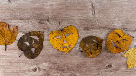 dry foliage on a wooden background. on the leaves made a scary mask. holiday of Halloween