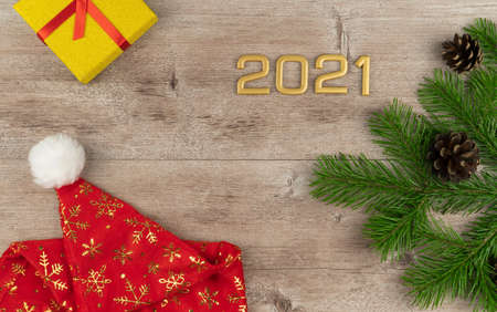 red hat of Santa Claus and spruce. new year 2021. fir branches with cones on a wooden background. Stock Photo