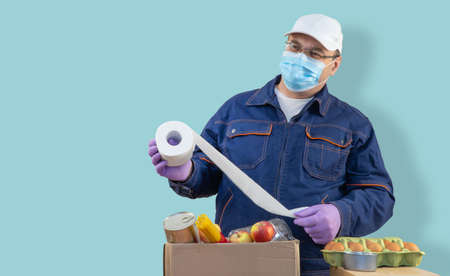 Delivery man puts products in a paper bag and carton box. selective focus. volunteer is wearing special clothing, a protective medical mask and rubber gloves. delivery of essential products.
