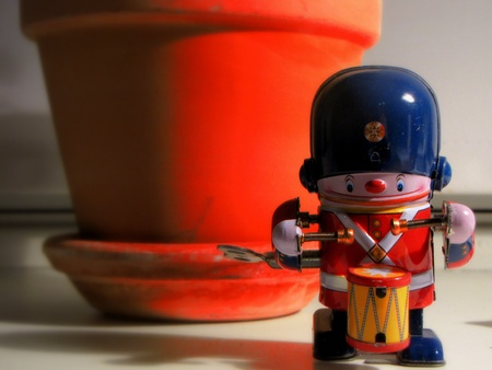 Little toysolder plays the drum in front of a pot photo