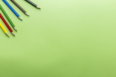 Multicolor pencils at green background. Black, brown, blue, green, red, yellow pencils at green paper background