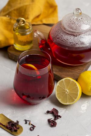 Transparency glass of hibiscus tea (karkade, Agua de flor de Jamaica) with lemon, glass teapot, honey with honey stick and orange napkin at light background. Fresh teatime composition. Concept of healthy lifestyle Foto de archivo - 119135788
