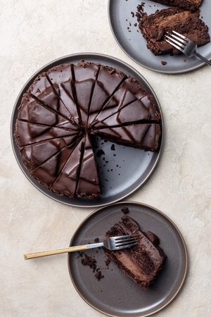 Top view concept of two pieces of chocolate cake with whole cake on gray plates at light background. Concept of holiday dessert Imagens