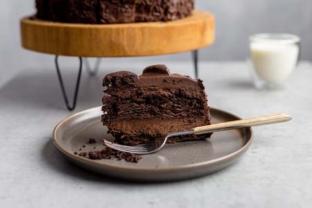 Tasty piece of chocolate cake on gray plate with fork, with whole cocoa cake on wooden stand, glass of milk near on gray background. Side view. Concept of birthday cake Stok Fotoğraf - 122729420