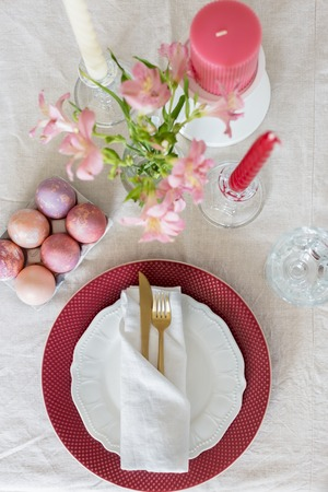 Easter flat lay serving plate with red and white plates, white napkin, gold tableware and eggs, glass and candles. Table top, concept of Easter holiday table setting. Фото со стока
