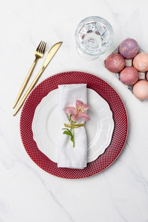 Serving plate for Easter breakfast with fork, knife and painted eggs on marble background. Concept of Easter food. Table top, flat lay, concept of holiday decor