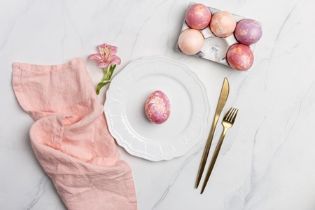 Easter table, place setting. Easter egg, pink color painted in a white plate, pink napkin, golden tableware with flower on white marble background, vertical, copy space, top view. Concept of Easter background Reklamní fotografie