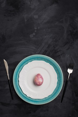Serving plate for Easter and other holidays. Fork and knife on white and blue plates, pink egg on plate at dark background. Concept of holiday table setting Imagens