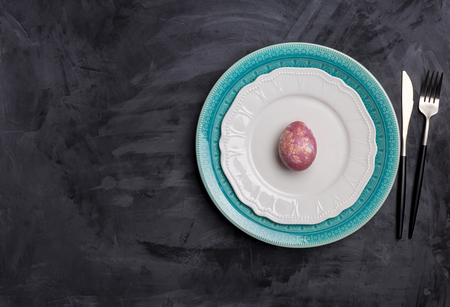 Serving plate for Easter and other holidays. Fork and knife on white and blue plates, pink egg near on black background. Concept of holiday table setting. Free space for text